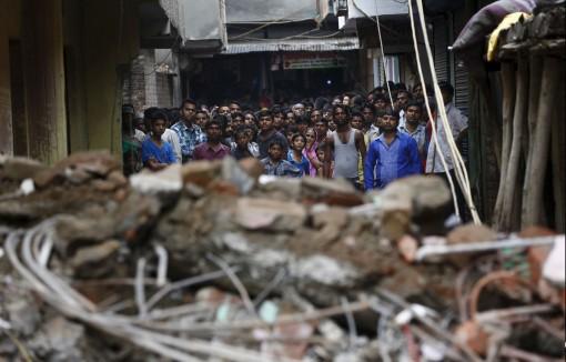 """Grup de cetățeni în New Delhi... Suprinși de ceva banal - o clădire de cinci etaje s-a prăbușit. Nu e nici prima și nu va fi nici ultima - dar surpriza pare a fi sinceră: """"Câte blocuri vor mai trebui să cadă, până-nvățăm să construim corect?"""""""